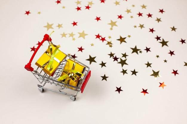 ギフト、光沢のあるクリスマスの装飾が施された買い物かご。販売、ギフトの購入。正月とクリスマスのブラックフライデーフラットレイ。
