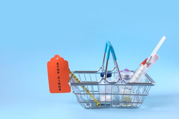 Корзина для покупок со шприцами, инъекциями, вакцинами и пробирками с кровью на синем фоне и надписью stop virus. концепция вакцинации
