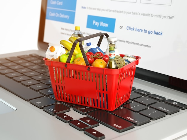 Shopping basket with variety of grocery products on laptop keyboard