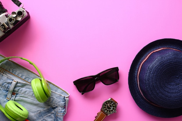 Shopping cap, glasses, watch, clothes, camera, headphones, music on the floor, pink top.