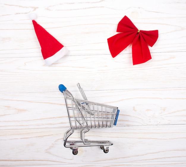 ショッピングカート、サンタ帽子、白い木製の赤いクリスマス弓