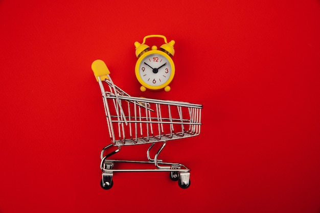 Shopping cart and alarm clock isolated on red.