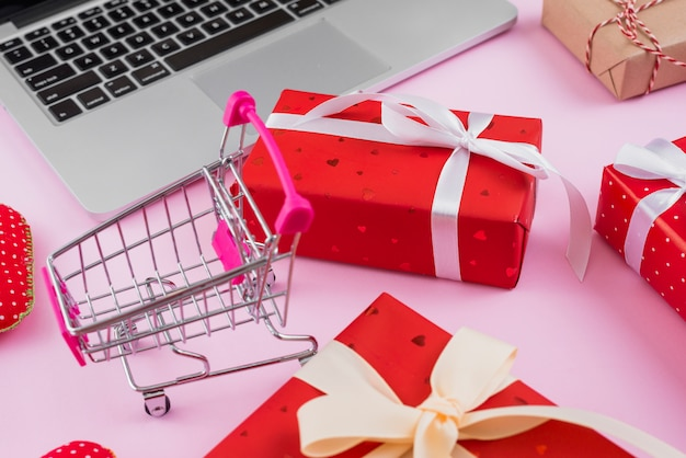 Shopping cart amidst gifts and modern laptop