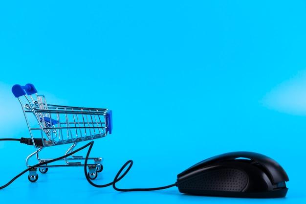 Магазинная тележкаа и компьютерная мышь, концепция интернет-покупок. скопируйте пространство.
