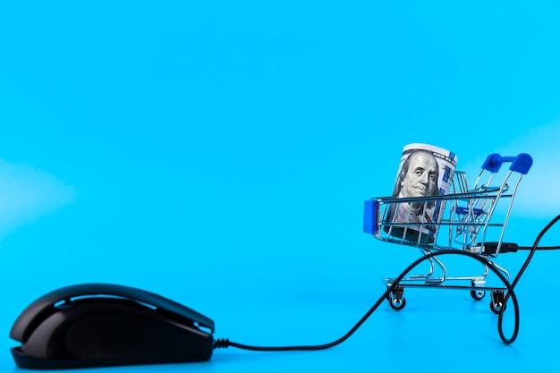 Магазинная тележкаа и компьютерная мышь, катите стодолларовые банкноты онлайн-концепции покупок. скопируйте пространство.