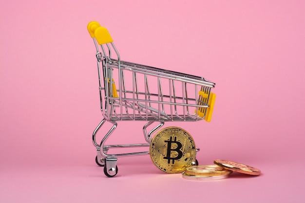 분홍색 배경에 쇼핑 카트 및 cryptocurrency 동전
