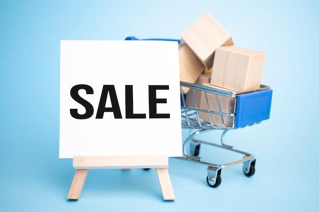 Корзина и мольберт со знаком продажи. концепция продажи