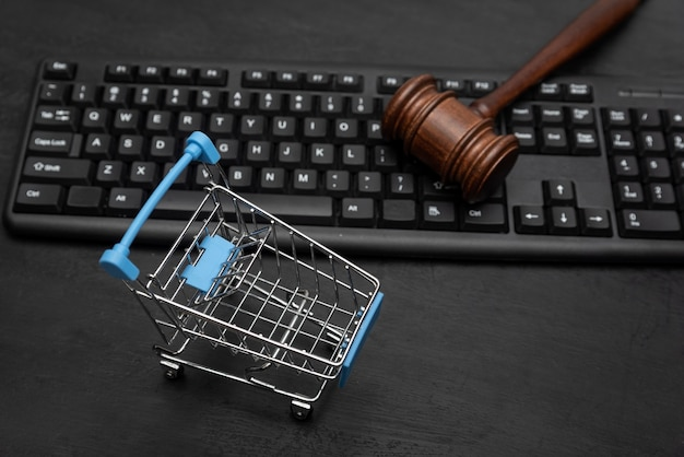 Тележка для покупок и молоток судьи на клавиатуре. судебная тяжба с продавцом. черный фон.