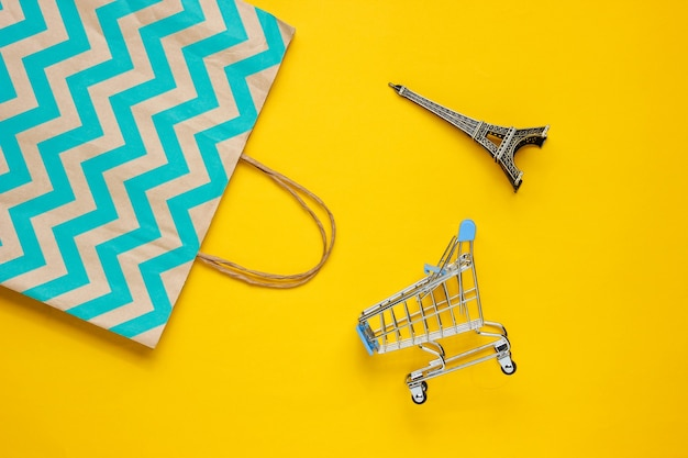 Корзина и бумажный пакет на желтом фоне. концепция счастливого клиента. интернет-магазины. онлайн магазин. потребительство, образ жизни