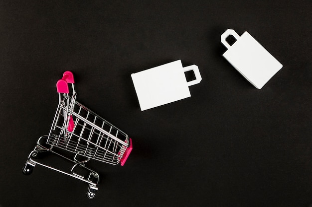 Shopping cart and bags on black background