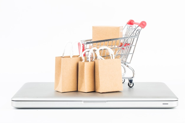 Shopping cart, bags and boxes over laptop, online store concept