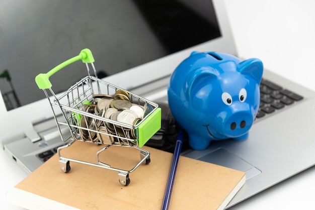 Shopping cart. coin in the cart with piggy bank and wallet on notebook and laptop background. online shopping, saving investment, purchase, business concept.