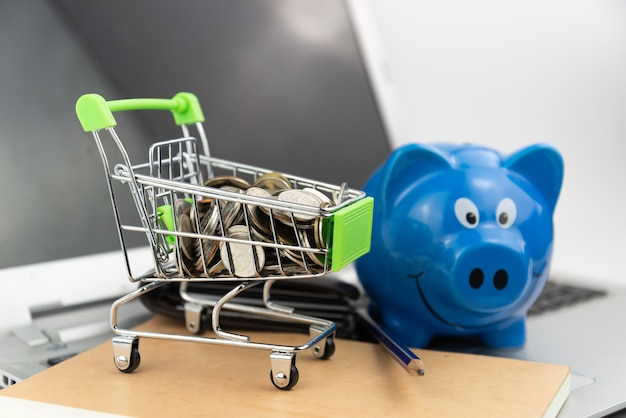 쇼핑 카트. 돼지 저금통과 노트북 및 노트북 배경에 지갑 장바구니에 동전. 온라인 쇼핑, 저축 투자, 구매, 비즈니스 개념.