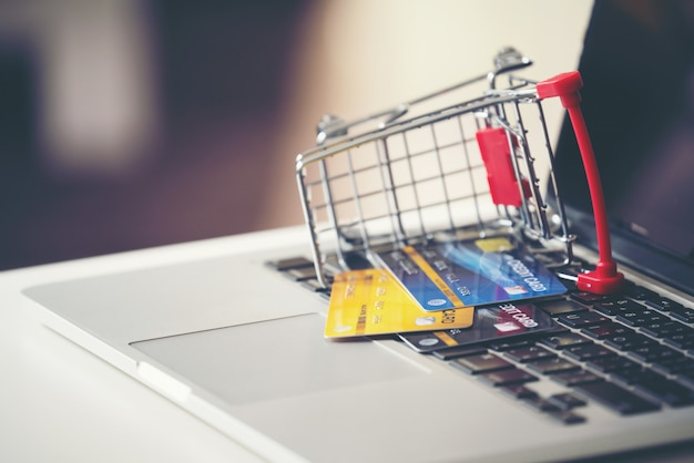 Shopping cart and credit card with laptop on the desk