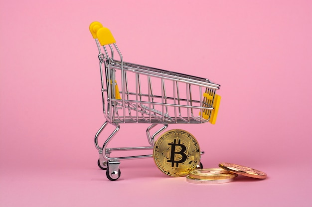 Shopping cart and cryptocurrency coins on a pink background