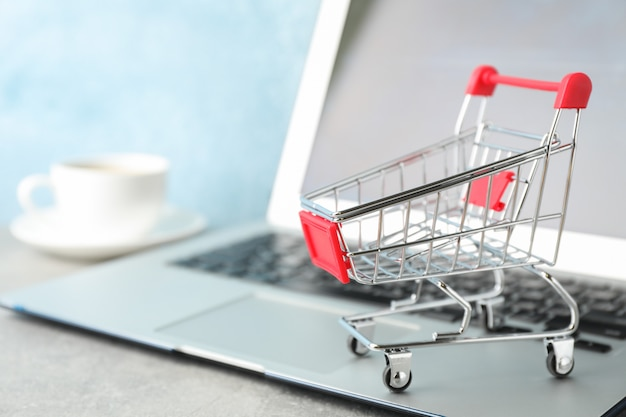 Shopping cart, cup of coffee and laptop copy space
