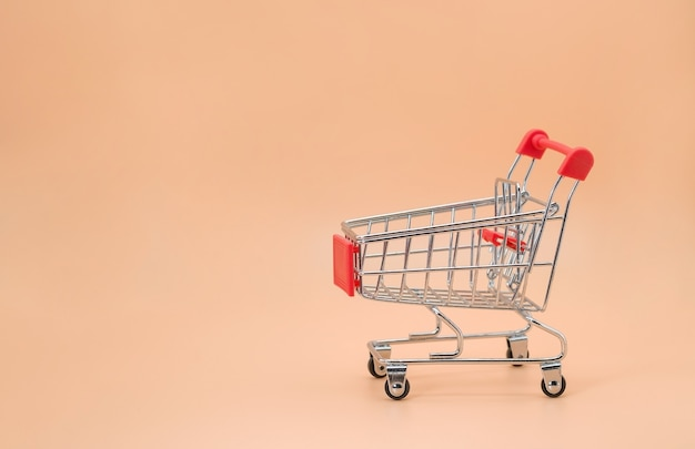 Shopping cart empty with copy space on beige background