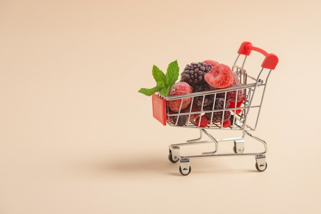 A shopping cart filled with frozen berries on a beige surface with space for text