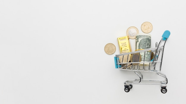 Shopping cart filled with money copy space
