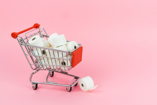 A shopping cart filled with toilet paper on a pink background. covid-19 concept. copy space.
