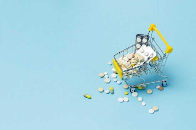 Shopping cart from the supermarket full of pills on a blue background.