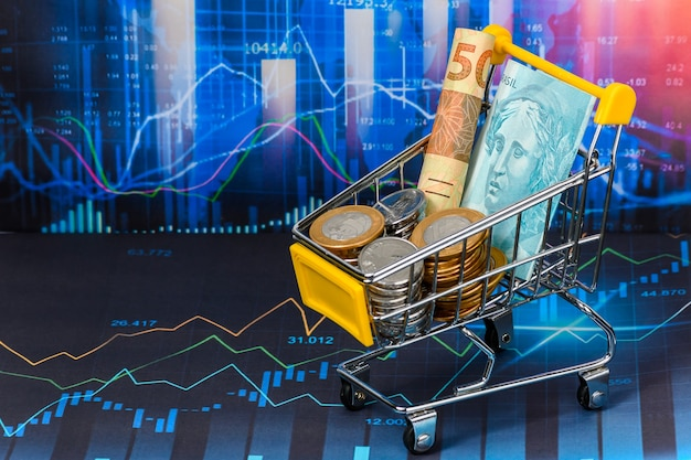Shopping cart full of brazilian money on financial market graph