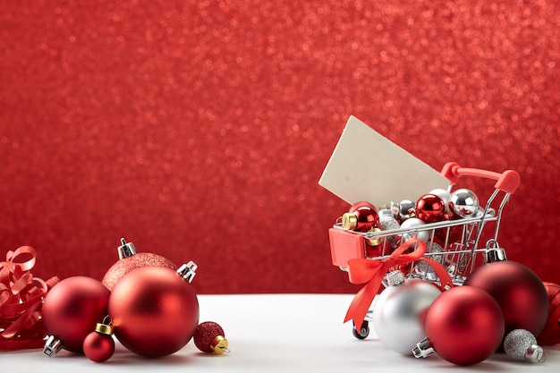 Shopping cart full of christmas ornaments on red background