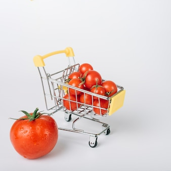 Shopping cart full of fresh red tomatoes on white backdrop