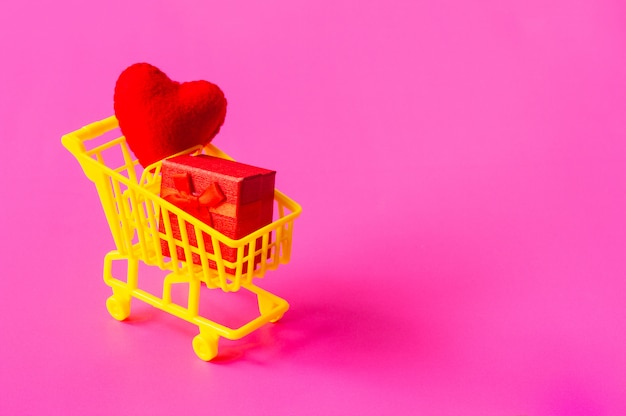 Shopping cart full of gifts of different colors on a pink background, with a negative space