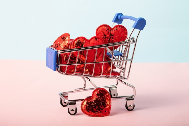 Shopping cart full of glossy red heartsconcept of the saint valentines day