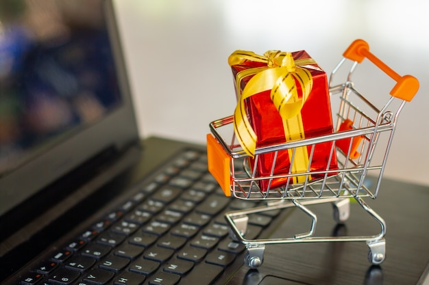 Shopping cart full of gold gift boxes and red sale sign through laptop monitor