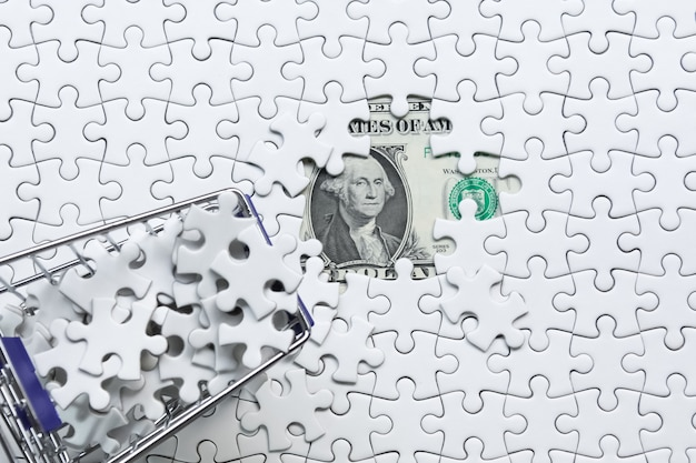Shopping cart full of jigsaw puzzle on money dollar background, business solution concept ,key for success