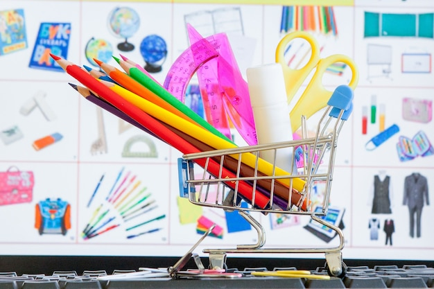 키보드, 온라인 쇼핑 개념에 학교 도구로 가득 찬 쇼핑 카트.