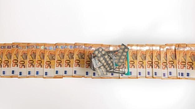 白で隔離された50ユーロ紙幣からのタブレットでいっぱいのショッピングカート、コピースペース