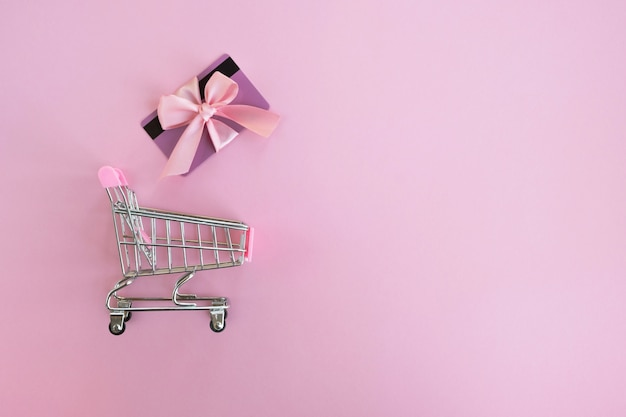 Shopping cart and gift card on pink surface