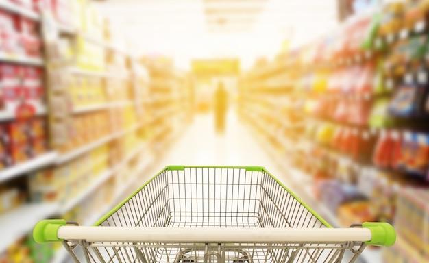 ぼやけたスーパーマーケットの背景のショッピングカート