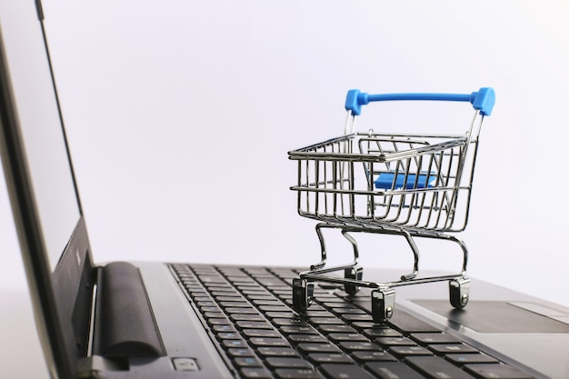 Shopping cart is on the laptop. online sales concept.