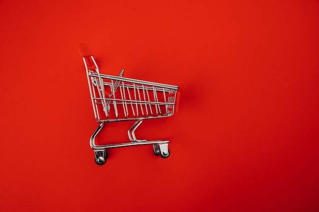Shopping cart isolated on red background.