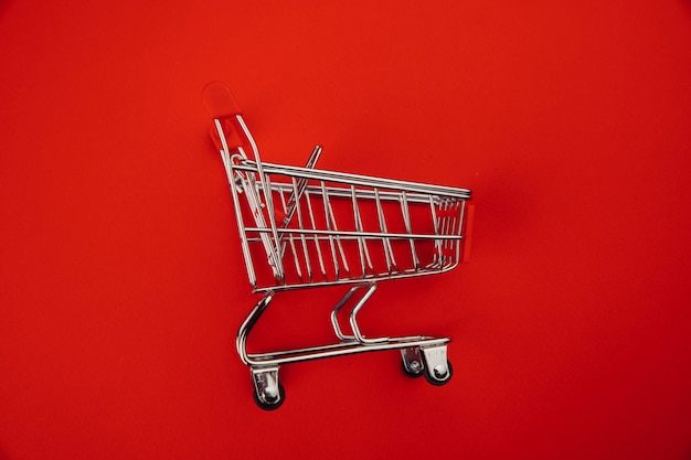 Shopping cart isolated on red