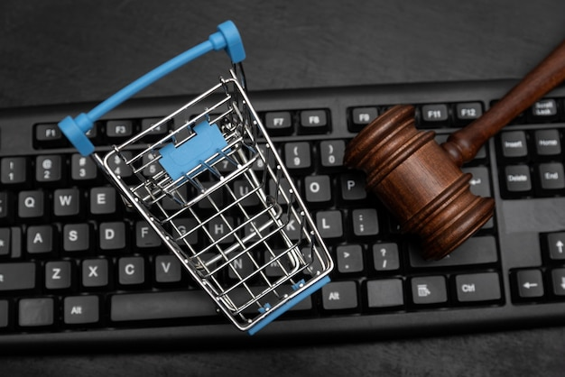 Shopping cart and judges hammer on the keyboard. online auction.