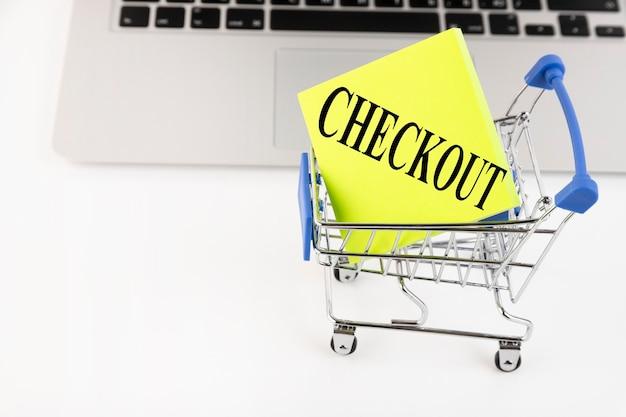 Тележка для покупок, ноутбук, текст, проверить, на желтой бумаге. бизнес