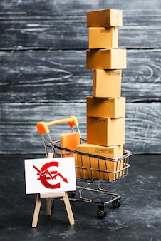 A shopping cart loaded with boxes and a sign with a euro symbol down arrow. decrease in income