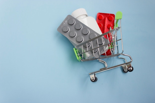 Shopping cart loaded with pills on blue background. the concept of medicine and the sale and delivery of drugs. copy space.
