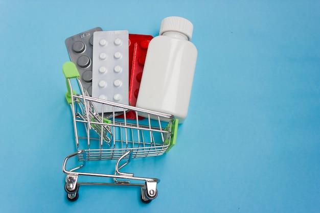 青い背景に錠剤を積んだショッピングカート。薬の概念と薬の販売と配達。スペースをコピーします。