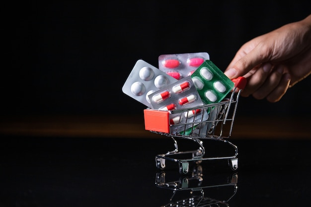 暗い背景に薬を入れたショッピングカート。ショッピング医学のコンセプト