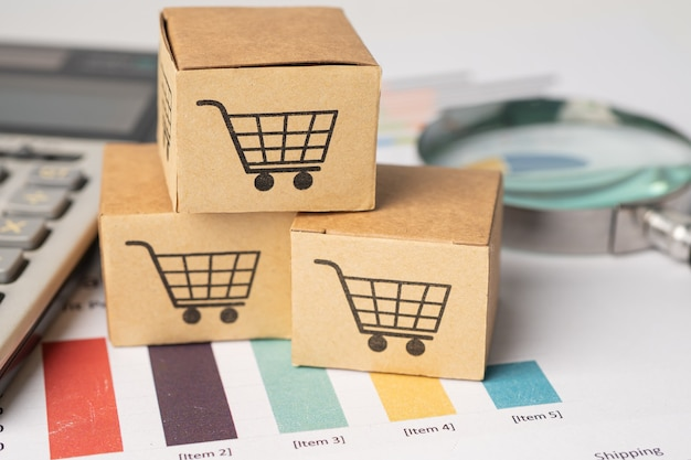 Shopping cart logo on box with magnifying glass on graph background