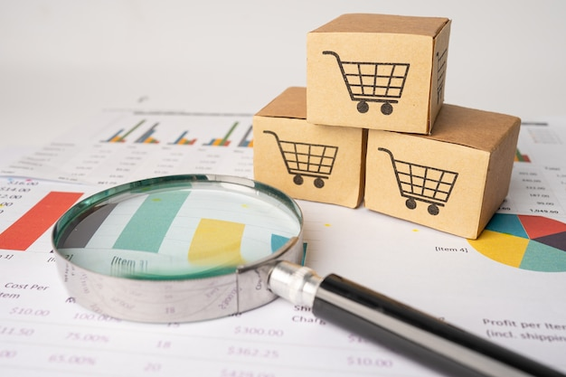 Shopping cart logo on box with magnifying glass on graph