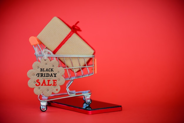 Shopping cart, mobile and gift box with black friday sale card
