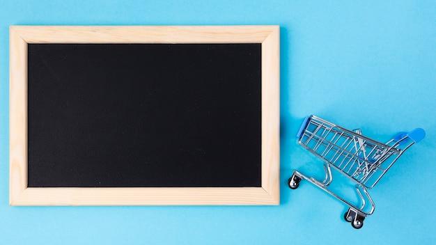 Shopping cart near blank blackboard