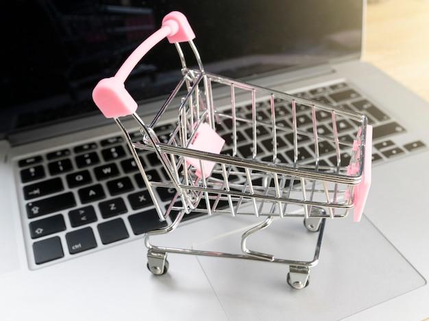 ノートパソコンの横にあるショッピングカート、オンラインショッピングのコンセプト